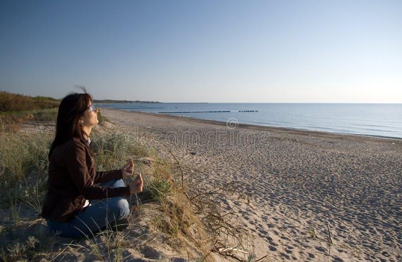 Yoga at sea. Woman practicing yoga at the sea or ocean stock photo