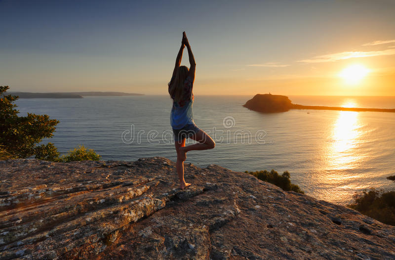 Yoga by the Sea at sunrise - Tree Pose Vrksasana royalty free stock photos