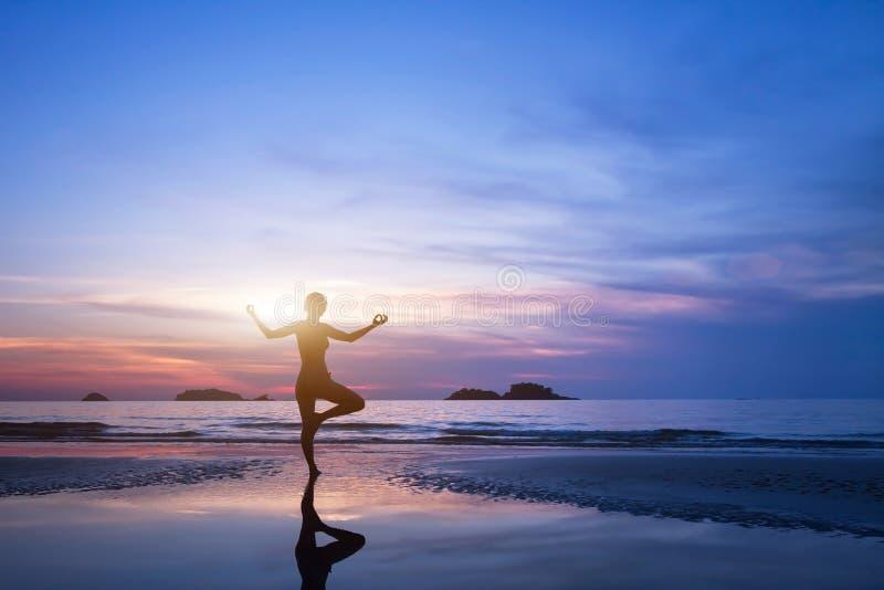 Yoga, silhouet van vrouw op het strand royalty-vrije stock afbeelding