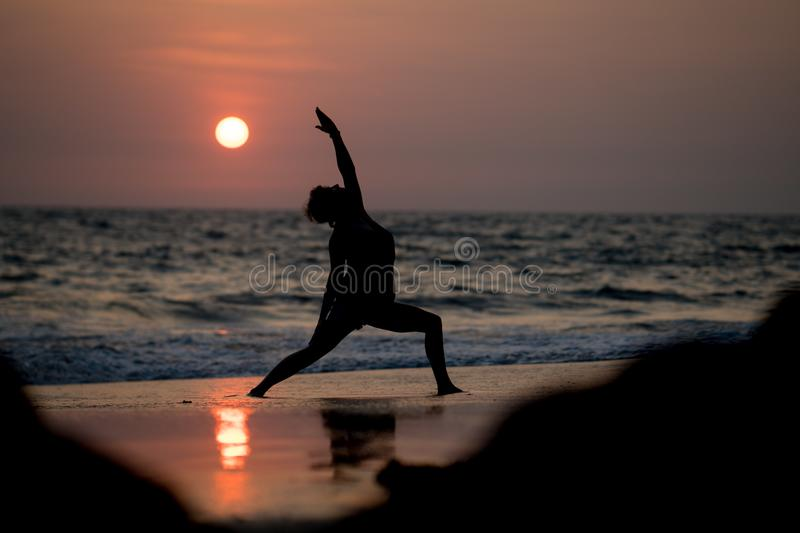 Yoga silhouette at ocean cost and sunset India stock photos