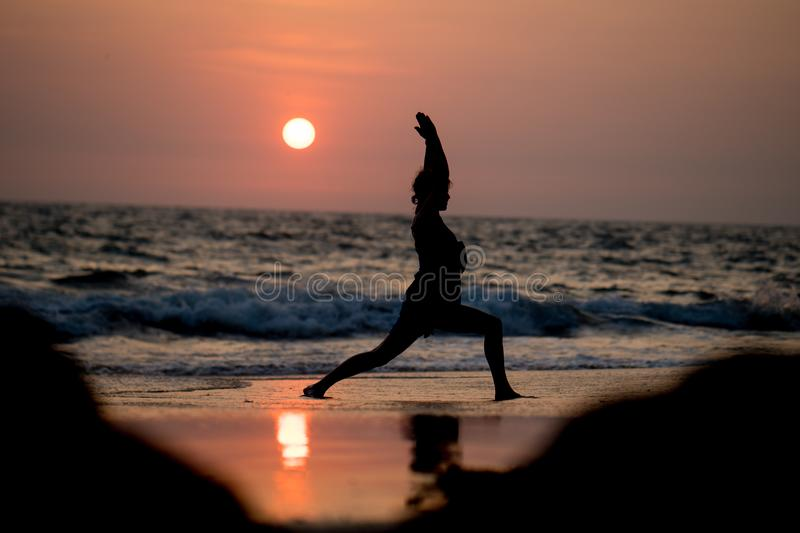 Yoga silhouette at ocean cost and sunset India stock image