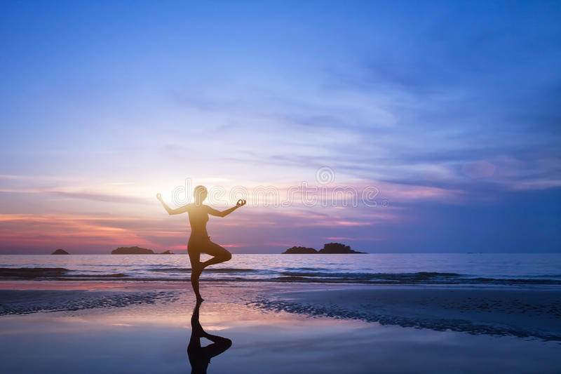 Yoga, silhouette of woman on the beach royalty free stock image