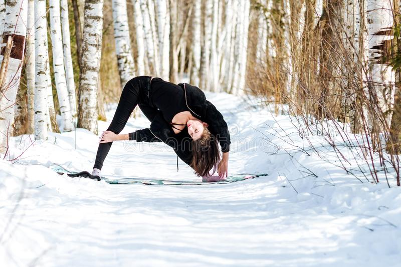 Yoga in the snow. Girl practicing yoga in the Park. Time of year winter. Snow-covered trees. stock image