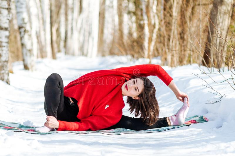 Yoga in the snow. Girl practicing yoga in the Park. Time of year winter. Snow-covered trees. stock images