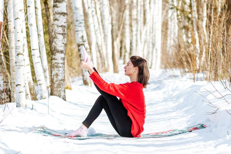 Yoga in the snow. Girl practicing yoga in the Park. Time of year winter. Snow-covered trees. royalty free stock images
