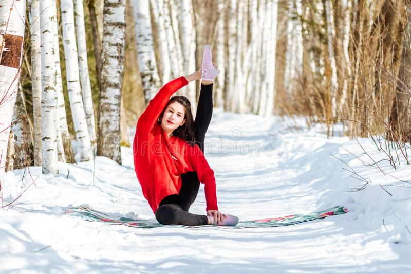Yoga in the snow. Girl practicing yoga in the Park. Time of year winter. Snow-covered trees. royalty free stock photo
