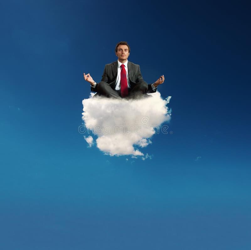 Yoga sollecitata di pratica dell'uomo d'affari su una nuvola immagini stock libere da diritti