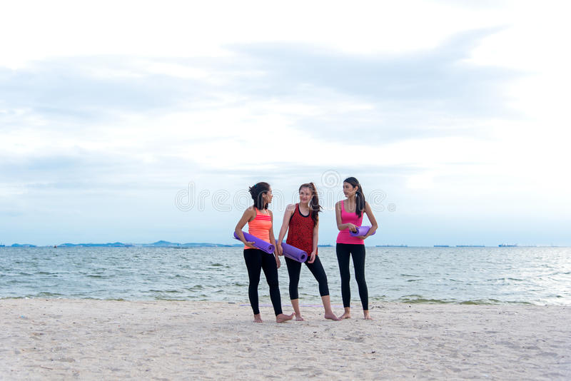 Yoga sonriente de las mujeres al aire libre en la playa Amigos atléticos jovenes de las mujeres con costa del fondo de las estera fotos de archivo