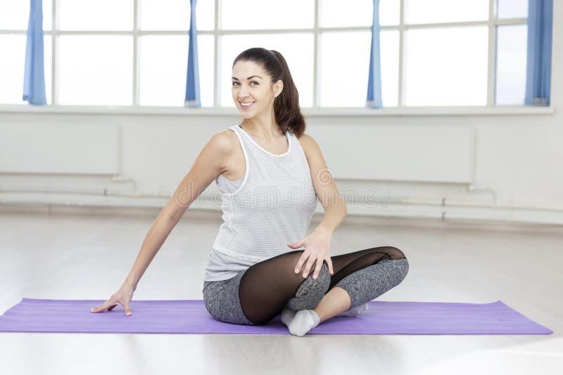 Yoga sonriente joven de las prácticas de la mujer en la manta en el pasillo imagen de archivo