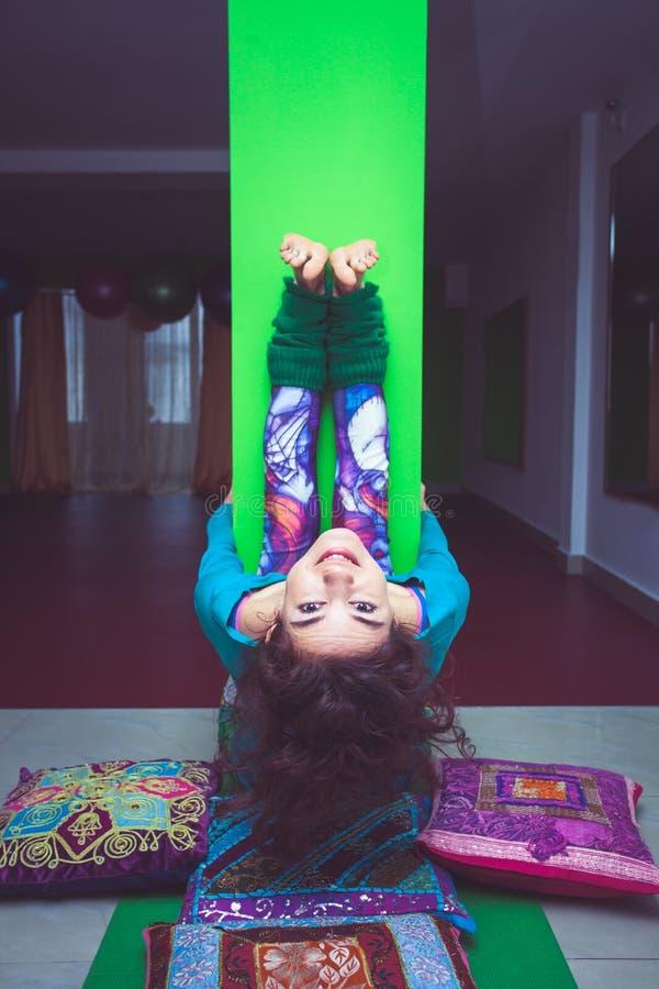 Yoga sorridente di pratica della donna che allunga contro la colonna fotografia stock