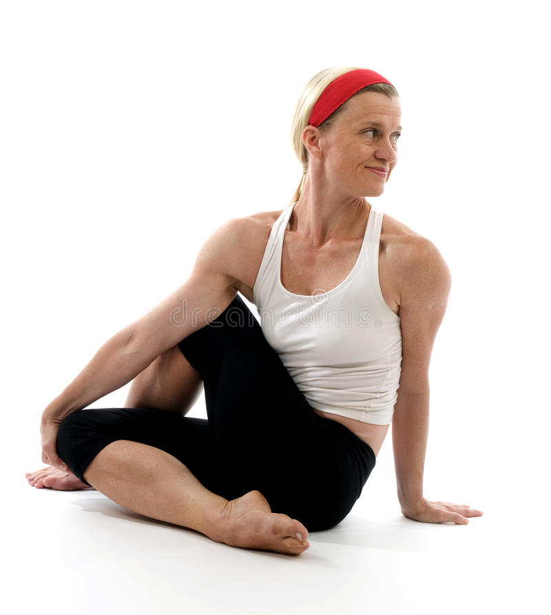 Yoga spine twisting illustration pose. Yoga spine twisting pose illustrated by attractive middle age fitness trainer teacher woman exercising and stretching royalty free stock photos