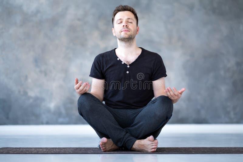 Yoga stelt de mannelijke beginner het praktizeren yogazitting binnen en mediteert royalty-vrije stock fotografie