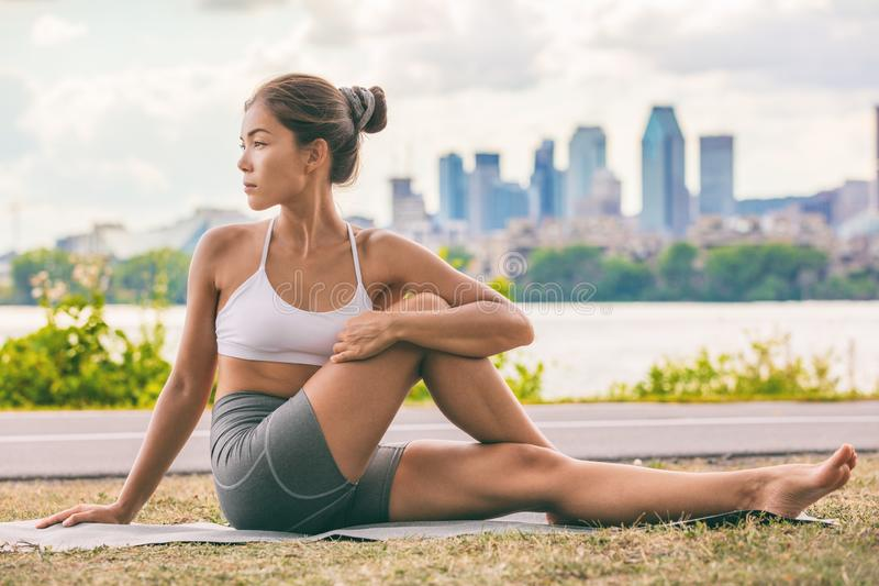 Yoga stretch exercise fit Asian woman stretching lower back for spine health on city outdoor fitness class in park. Seated spinal stock photo