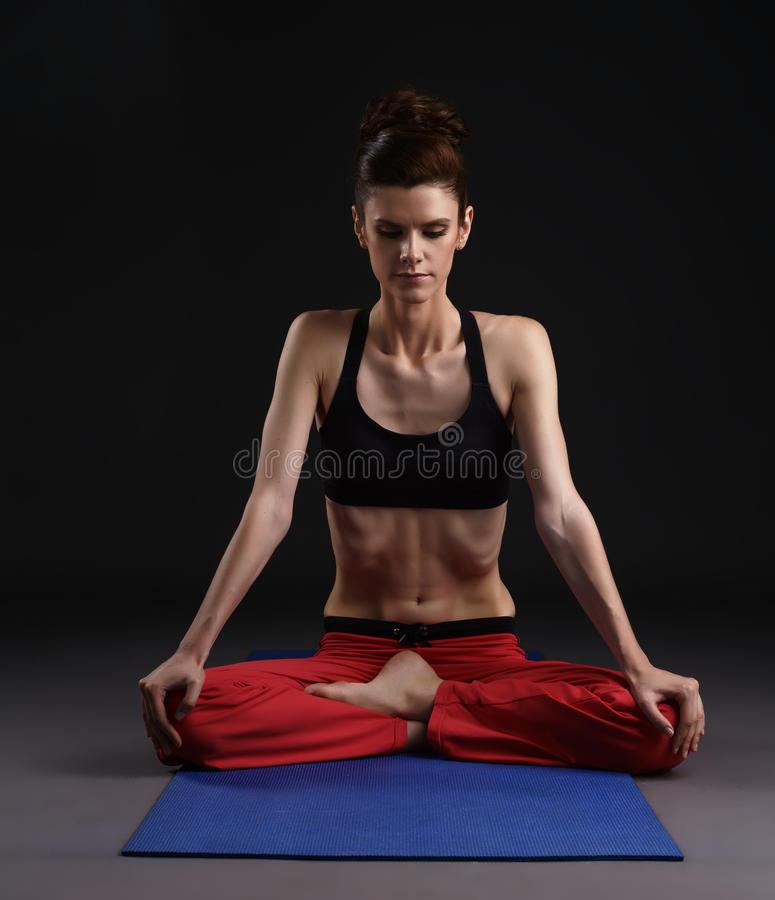 Yoga in studio. Woman doing breathing exercise stock photo