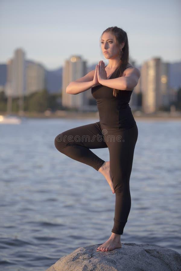 Yoga su una roccia alla spiaggia immagini stock libere da diritti