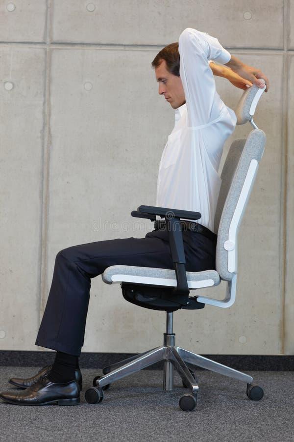Yoga sur la chaise dans le bureau - exercice d'homme d'affaires photos stock