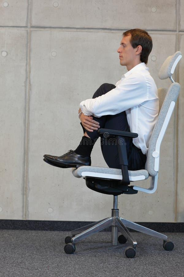 Yoga sur la chaise dans le bureau - exercice d'homme d'affaires images stock