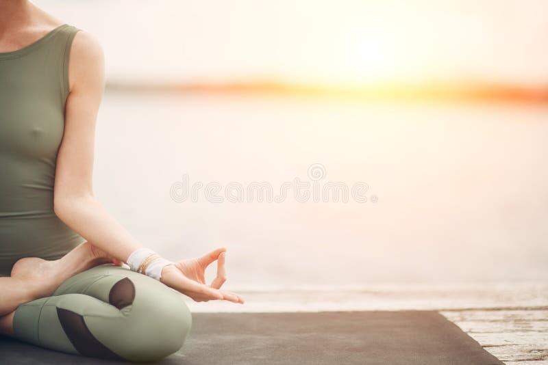 Yoga symbol. Lotus pose at the lake on sunset. Stylish modern woman royalty free stock photo