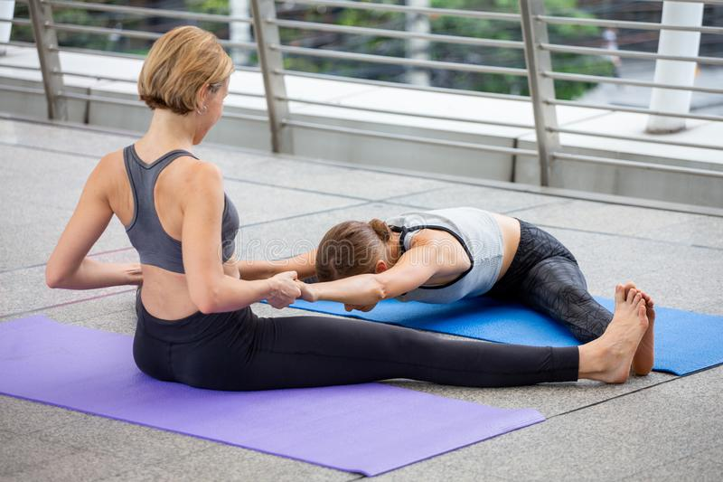 yoga teacher helping young fitness woman doing konasana or wide angle seated forward bend pose Pulling arms and spread leg. in stock photography