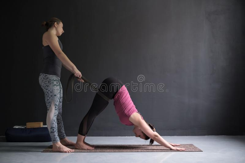 Yoga teacher or pilates instructor helping young woman to stretch muscles. stock image