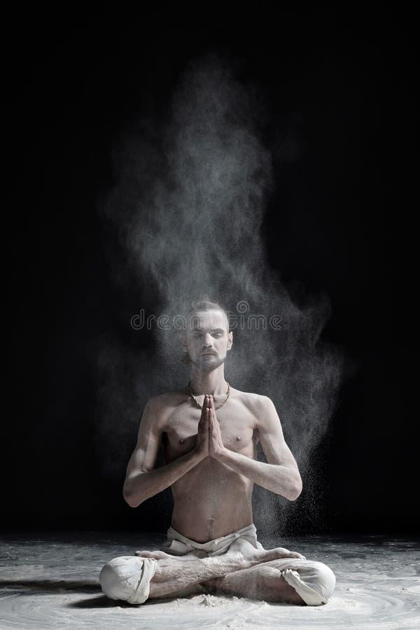 A yoga teacher sits in a sukhasana on a black background. stock image