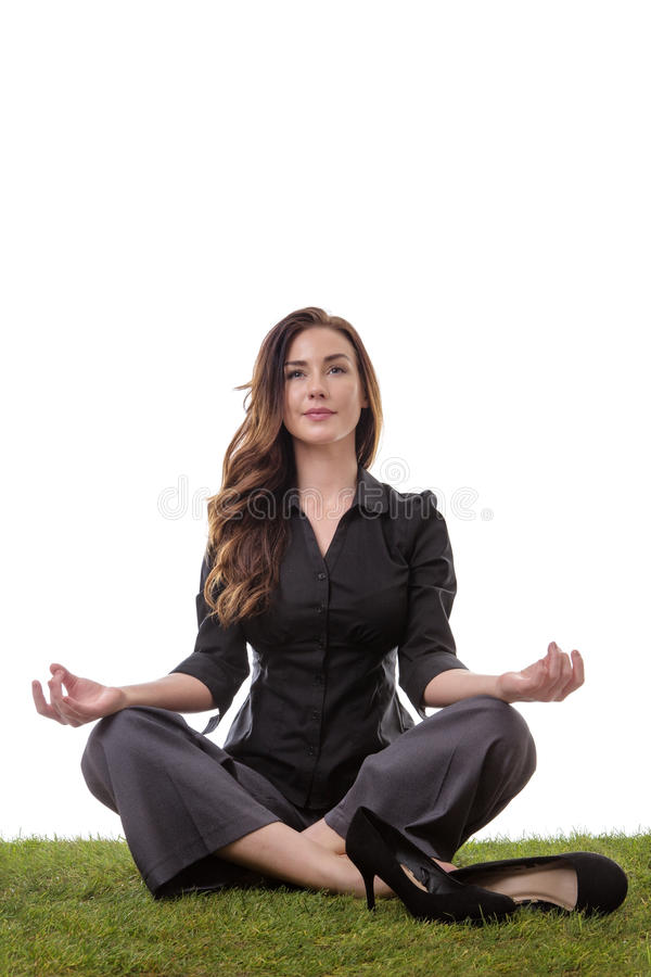 Yoga time. Pretty young business woman in a suit, sitting on grass in a crossed legs yoga pose, with her arms resting on her knees, palms upwards isolatd on royalty free stock photos