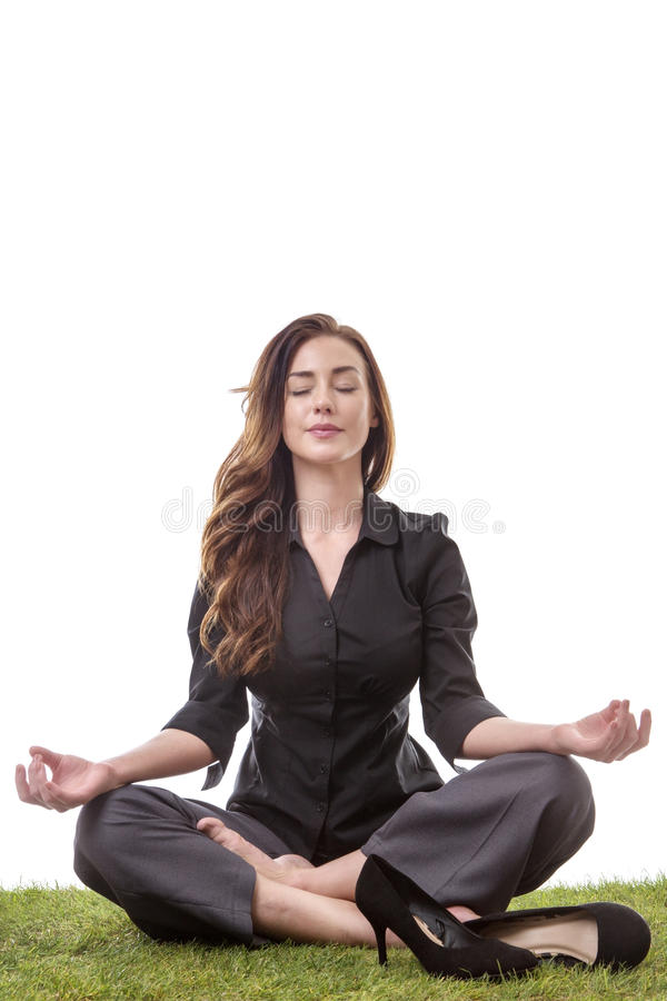 Yoga time. Pretty young business woman in a suit, sitting on grass in a crossed legs yoga pose, with her arms resting on her knees, palms upwards isolatd on royalty free stock photo