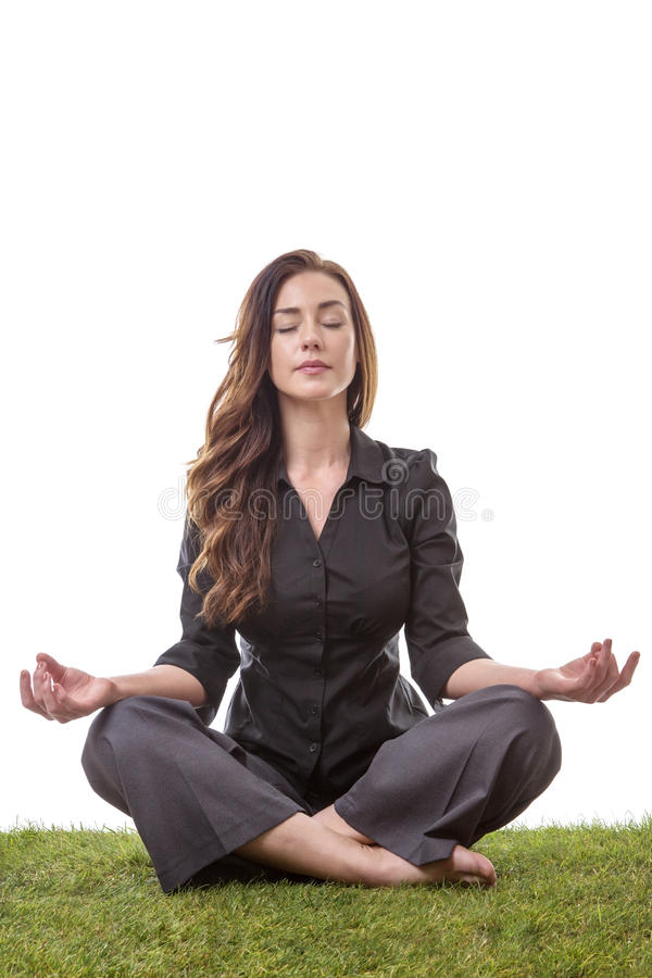Yoga time. Pretty young business woman in a suit, sitting on grass in a crossed legs yoga pose, with her arms resting on her knees, palms upwards isolatd on stock photos