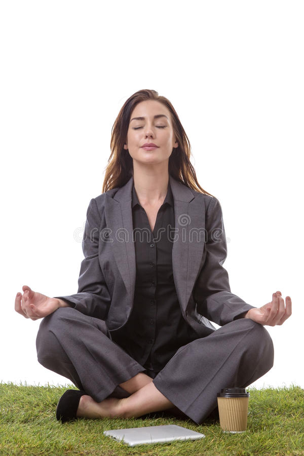 Yoga time. Pretty young business woman in a suit, sitting on grass in a crossed legs yoga pose, with her arms resting on her knees, palms upwards isolated on royalty free stock image