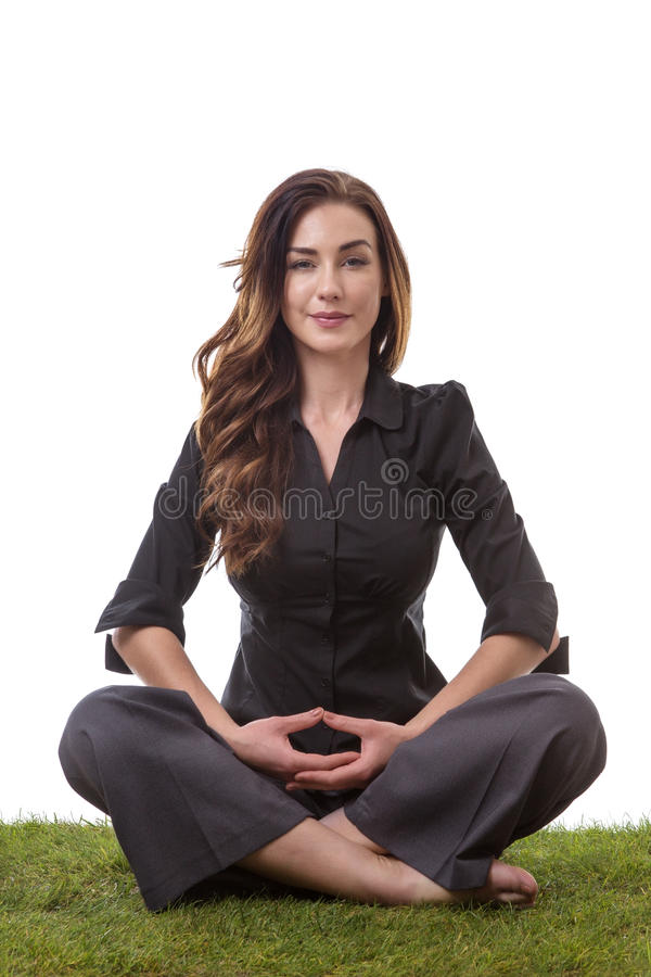 Yoga to relax. Pretty young business woman in a suit, sitting on grass in a crossed legs yoga pose, with her arms on her lap royalty free stock image