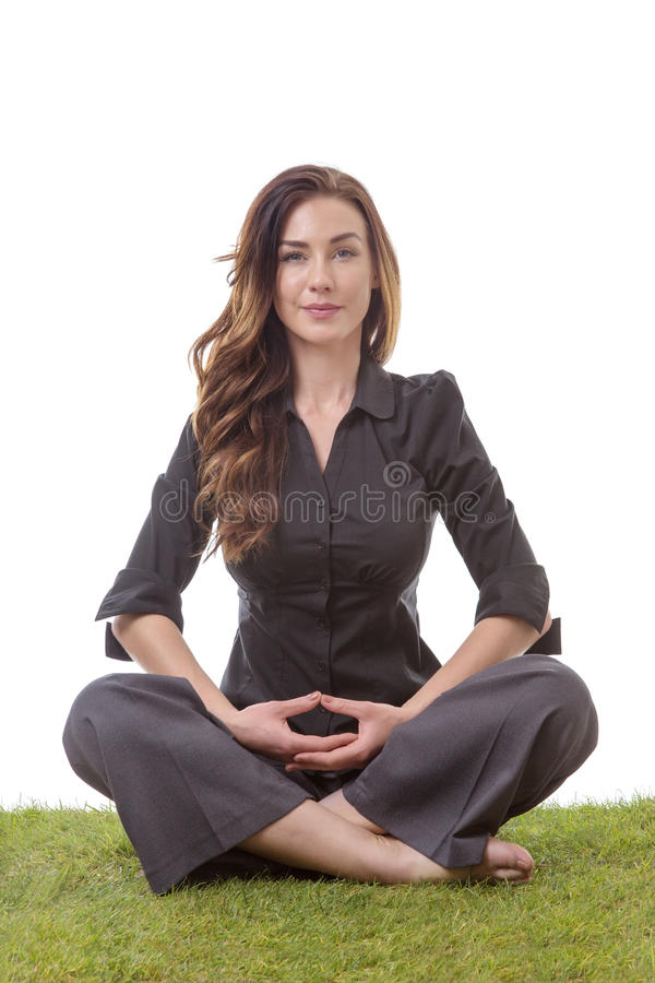 Yoga to relax. Pretty young business woman in a suit, sitting on grass in a crossed legs yoga pose, with her arms on her lap royalty free stock photo