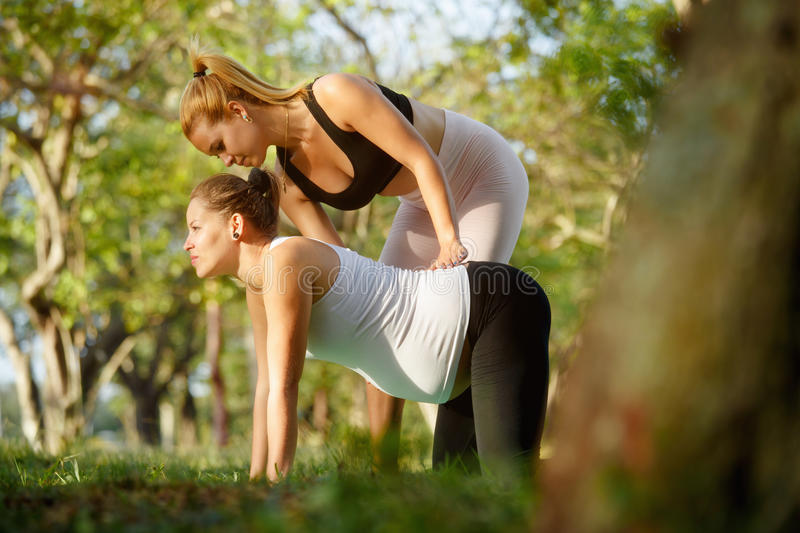 Yoga Trainer Helping Pregnant Woman With Exercise For Backpain. Mom with back pain, mother during pregnancy. Prenatal lesson in city park, antenatal class royalty free stock photo