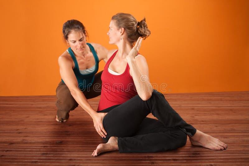 Yoga-Trainer mit Kursteilnehmer lizenzfreie stockfotos