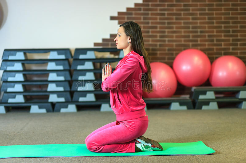 Yoga training. Beautiful white girl in a pink sports suit meditates on the yoga class at the fitness center. Young beautiful white girl in a pink sports suit stock image