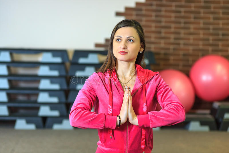 Yoga training. Beautiful white girl in a pink sports suit meditates on the yoga class at the fitness center. Young beautiful white girl in a pink sports suit stock photography
