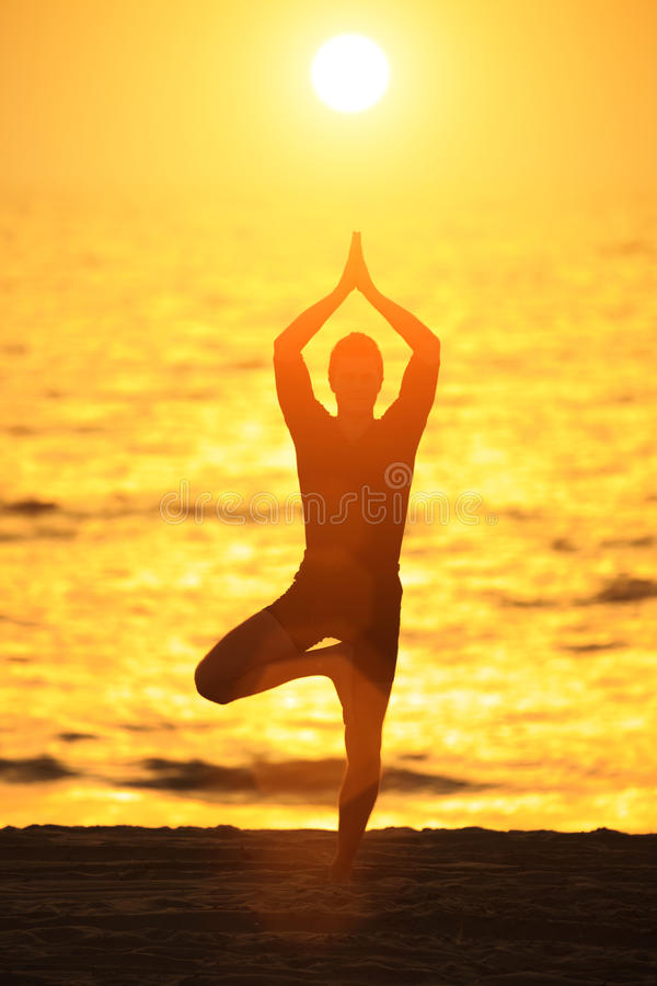 Yoga tree pose. Man standing in yoga tree pose on ocean beach at sunset royalty free stock photo