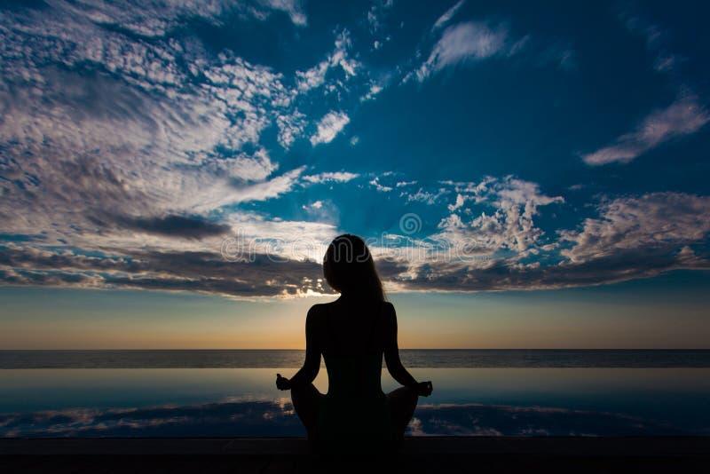 Yoga und gesunder Lebensstilhintergrund, abstraktes Schattenbild der Frau meditierend am Pool und Meer stockfotografie