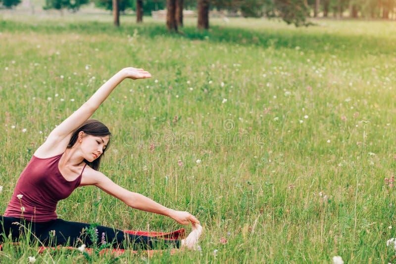 Yoga und Meditation in der Natur an einem sonnigen Tag Schönheit in Burgunder-Spitze auf dem Hintergrund von Feldern und von Wäld lizenzfreies stockbild