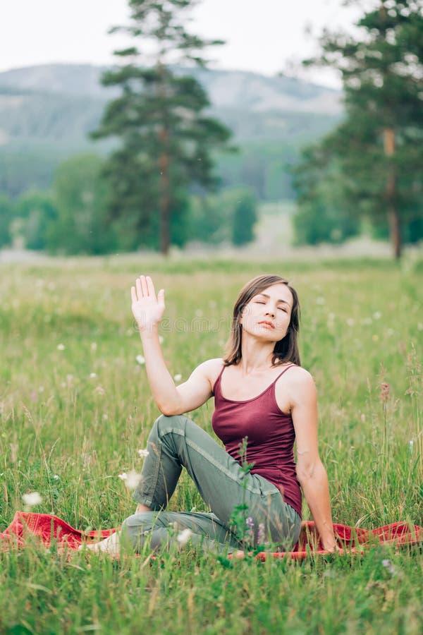 Yoga und Meditation in der Waldschönen Natur- und Brunettefrau, die in der Natur mit Augen meditiert, schlossen lizenzfreies stockfoto