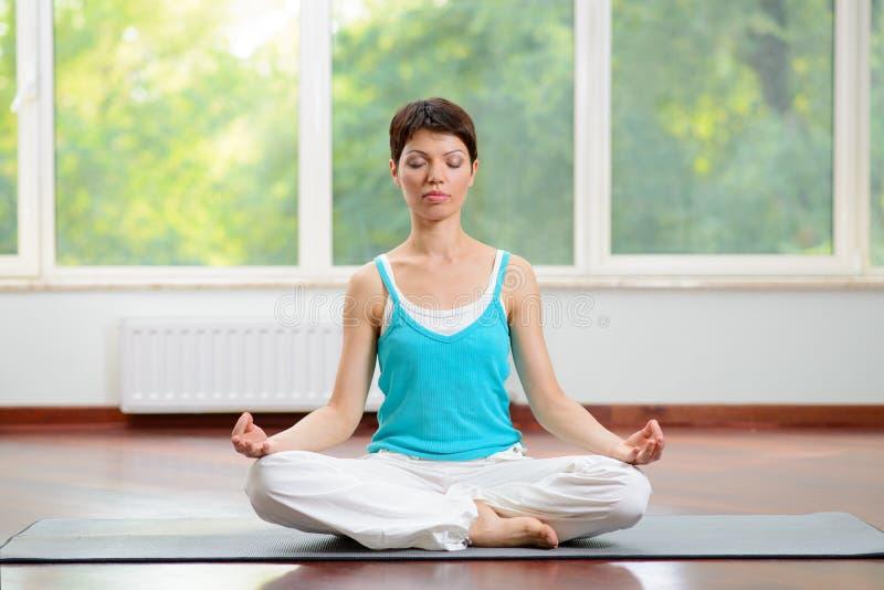 Yoga und Meditation zuhause Junge Frau, die auf Lotus Position sitzt und mit den Augen geschlossen meditiert lizenzfreie stockbilder