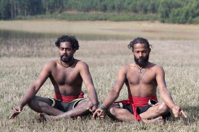 Yoga - uomini indiani che meditano nella posa di yoga del loto su erba verde nel Kerala, India immagine stock libera da diritti