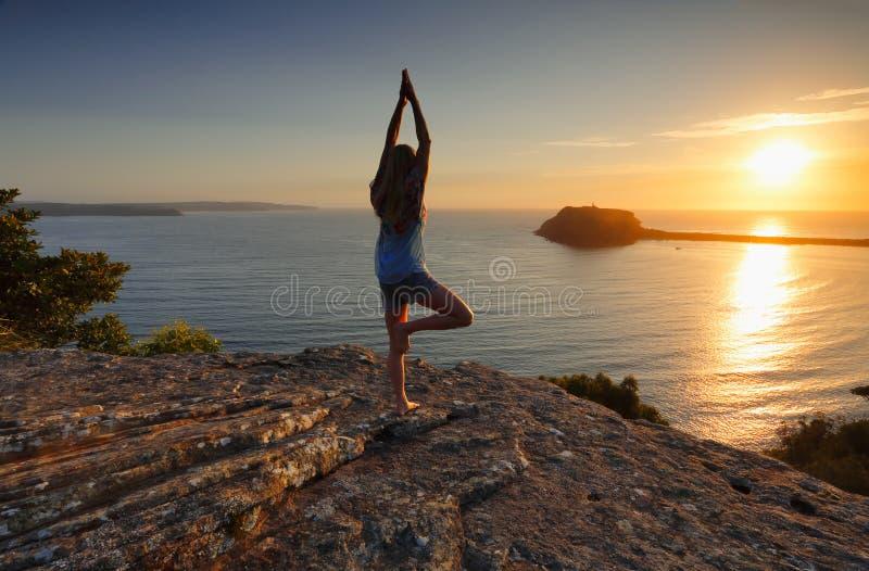 Yoga vid havet på soluppgång - trädet poserar Vrksasana royaltyfria foton