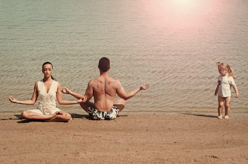 Yoga voor de gehele familie de familie van gelukkige kind, mens en vrouw die, yoga stelt de mediteren stock foto's