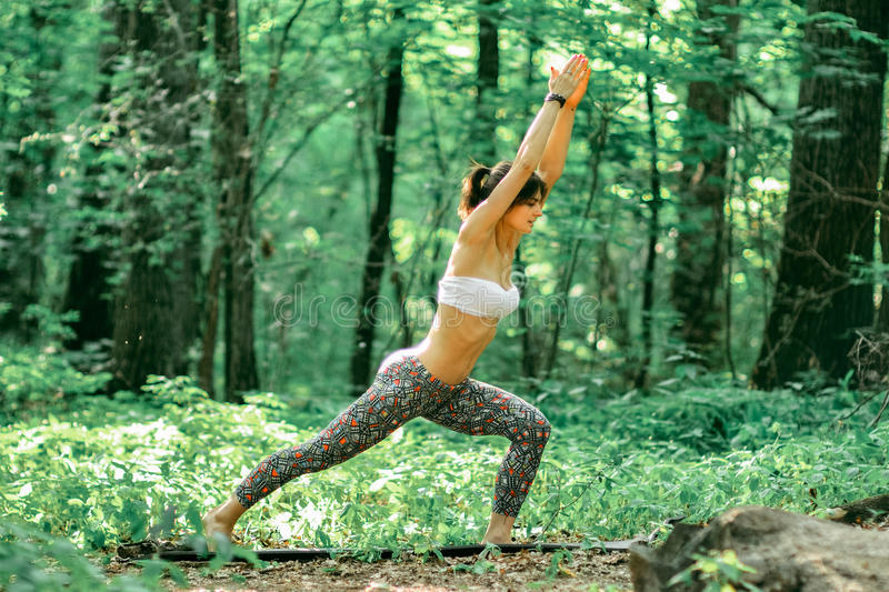 Yoga warrior pose by woman on green grass in the park around pin. E trees outdoors stock photos