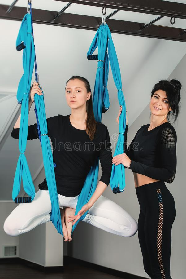 Yoga in a white room. Girls performs physical exercises fly-yoga, pilates on a special equipment stock photo