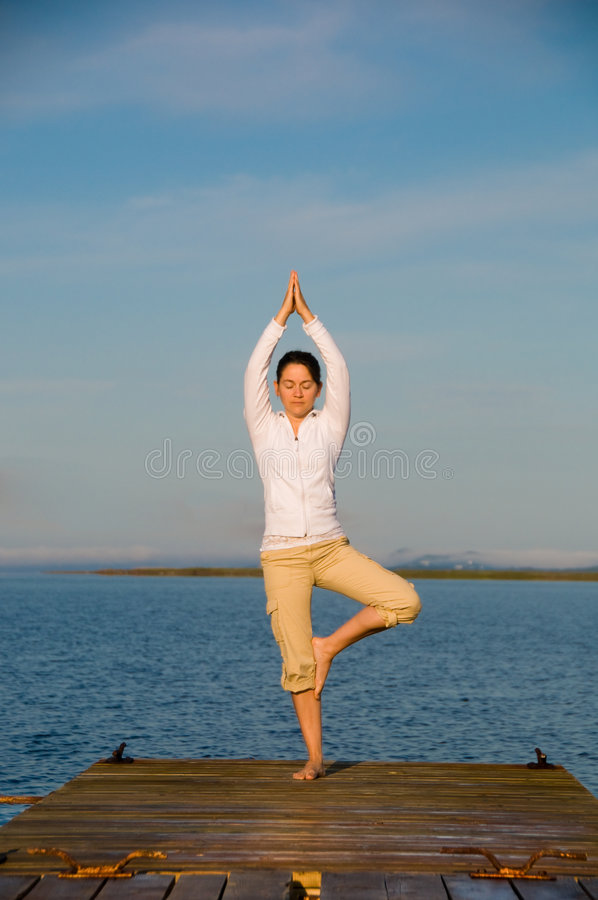 Yoga Woman. On a dock by the ocean royalty free stock image