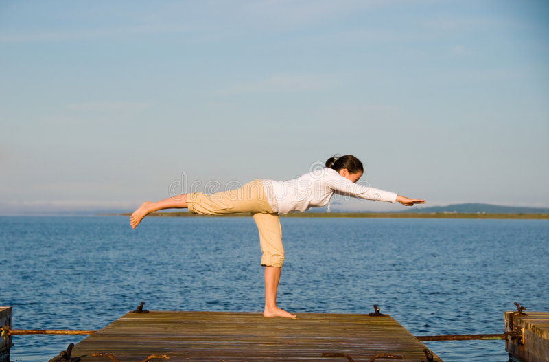 Yoga Woman. On a dock by the ocean stock images