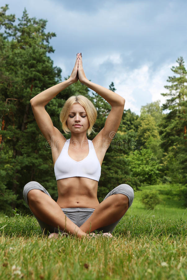 Yoga woman on green park. Beautiful young woman doing yoga exercise. Outdoor sport stock images