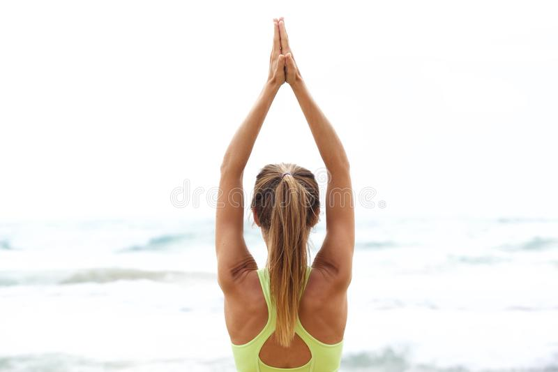 Yoga woman with hands up by the sea. Behind portrait yoga woman with hands up by the sea stock photos