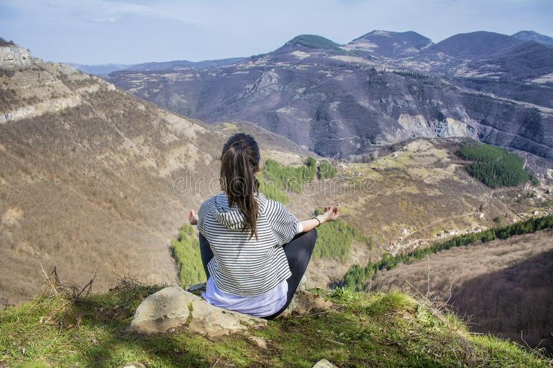 Yoga Woman Meditating in the Mountain. Young girl doing yoga fitness exercise outdoor on a beautiful mountains landscape stock images